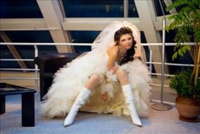Attractive bride with knee boots on showing legs