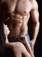 woman on knees undoing mans pants